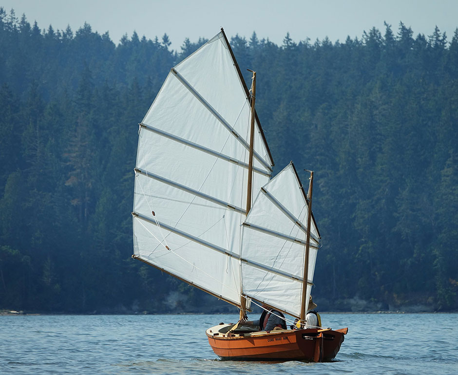 Small junk rigged sailboat going downwind.